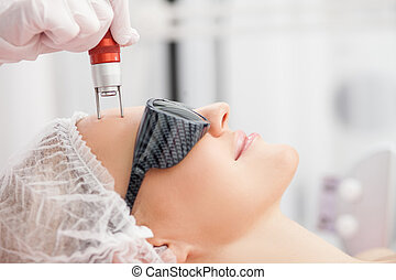 Cheerful skillful cosmetologist is treating female face - ...