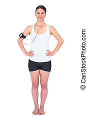 Cheerful slender model wearing armband holding mp3 player