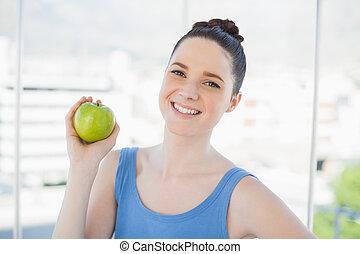 Cheerful slender woman in sportswear holding green apple