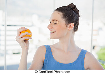 Cheerful slender woman in sportswear holding orange