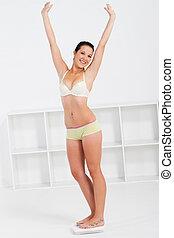 cheerful slim woman on scale