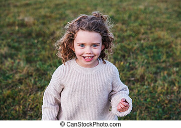Cheerful small girl standing in autumn nature, looking at camera.