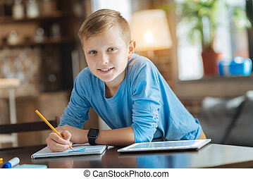 Cheerful smart boy leaning on the table