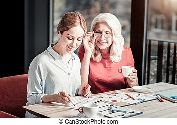 Cheerful smart women making notes in a calendar and smiling