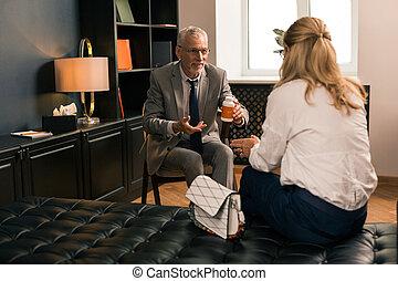 Friendly senior psychologist holding a box of pills
