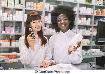 Cheerful smiling African and Caucasian women pharmacists are posing near table with cashbow in apothecary, showing medicines to camera. Welcome to the pharmacy