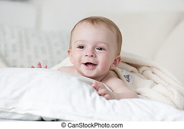 Cheerful smiling baby boy relaxing on big white pillow on bed