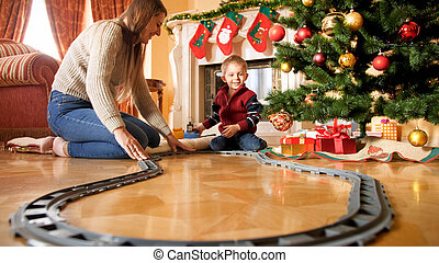 Cheerful smiling boy with young mother building railroad around Christmas tree at living room. Child receiving presents and toys on New Year or Xmas