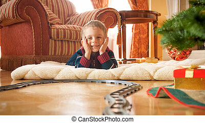 Cheerful smiling little boy looking on circle railroad under Christmas tree at houe living room. Child receiving presents and toys on New Year or Xmas
