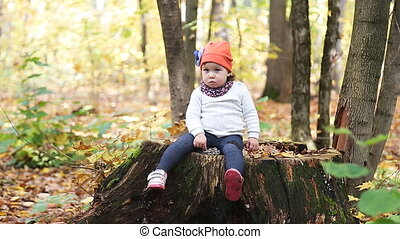 cheerful smiling little girl among autumn maple leaves
