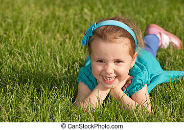 Cheerful smiling little girl on the green grass