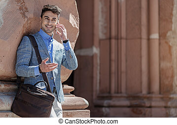 Cheerful smiling male person speaking on phone