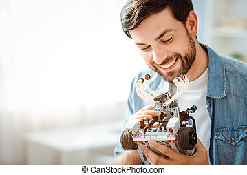 Cheerful smiling man holding robot