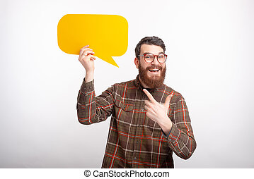 Cheerful smiling man pointing at a yellow bubble speech is standing on white background.