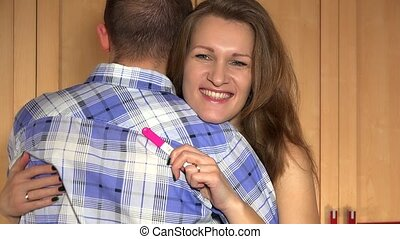 Cheerful smiling wife woman embrace her husband man with pregnancy test in hand