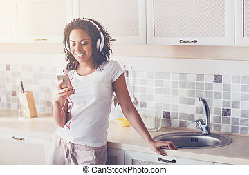Cheerful smiling woman resting in the kitchen