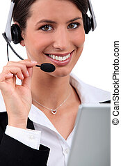 Cheerful, smiling woman with a headset and laptop