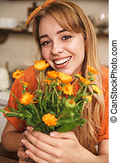 Cheerful smiling young blonde girl at the kitchen holding beautiful flowers in hands.