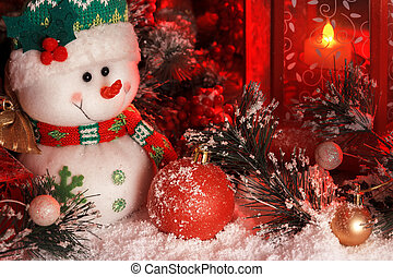 cheerful snowman and Christmas balls are covered with snow in the light of a red lantern on the background of New Year's scenery