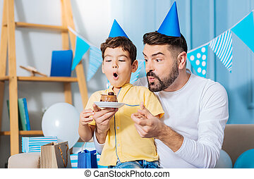 Cheerful son and father blowing out candle on birthday cake...