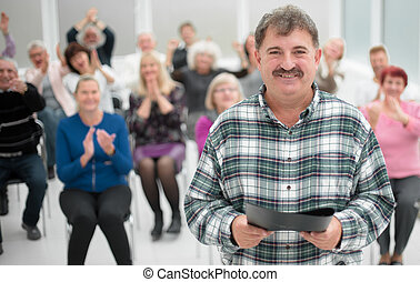 Cheerful speaker standing in conference hall and smilling at camera