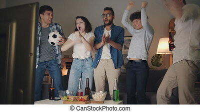 Cheerful sports fans watching football on TV doing high-five...
