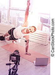 Cheerful sportsman doing stretching in front of camera