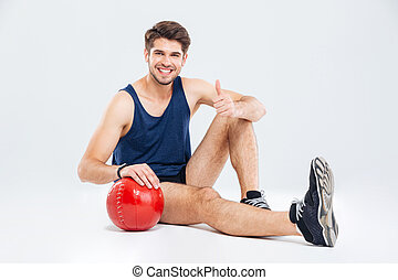 Cheerful sportsman with red ball sitting and showing thumbs up