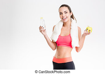 Cheerful sportswoman holding a bottle of water and an apple