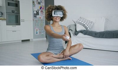 Cheerful sportswoman in VR glasses at home - Charming ethnic...