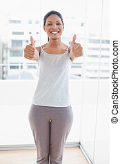 Cheerful sporty young woman giving thumbs up