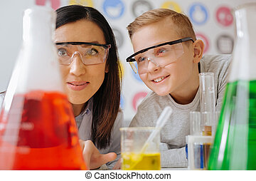 Cheerful student and his teacher watching chemicals react together
