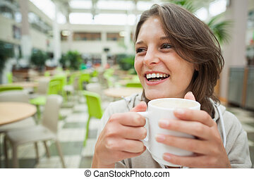 Cheerful student drinking coffee in - Close up of a cheerful...