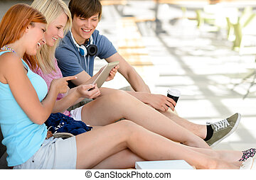 Cheerful student friends using tablet together