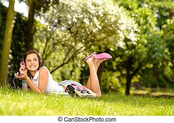 Cheerful student girl lying park listen music