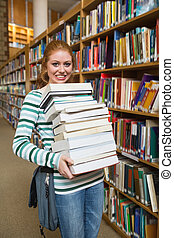 Cheerful student holding heavy pile of books standing in...