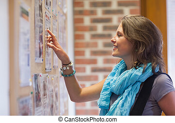 Cheerful student pointing at notice board