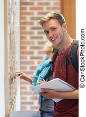 Cheerful student searching something on notice board