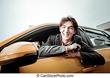 Cheerful student smiling broadly while sitting in his new car