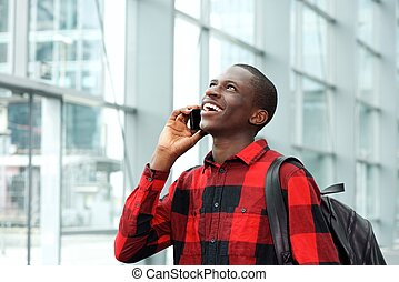 Cheerful student talking on cell phone at station