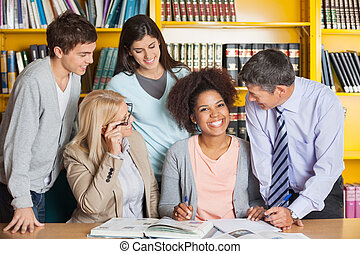 Cheerful Student With Teachers And Classmates In Library