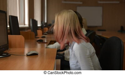 Cheerful student working on computer. A group of young...