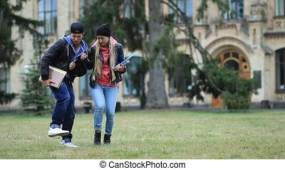 Cheerful students dancing on campus lawn