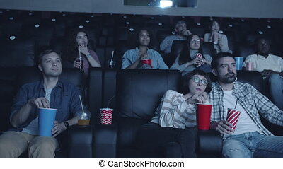 Cheerful students enjoying interesting movie in cinema sitting in dark room together looking at screen with happy faces. Modern culture and entertainment concept.