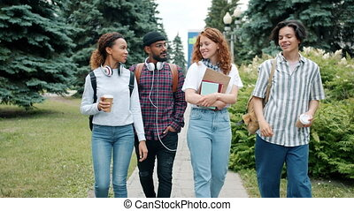 Cheerful students multi-ethnic group walking outdoors in ...