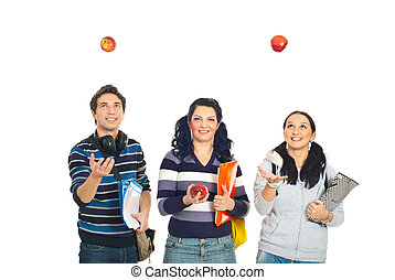 Cheerful students playing with apples