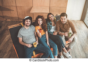 Cheerful students sitting on couch in lounge zone