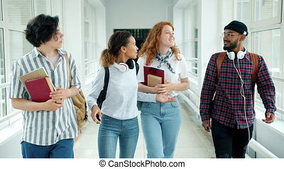Cheerful students multi-racial group are talking walking with books in college hall showing thumbs-up laughing. Emotions, lifestyle and education concept.