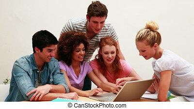 Cheerful students using laptop toge
