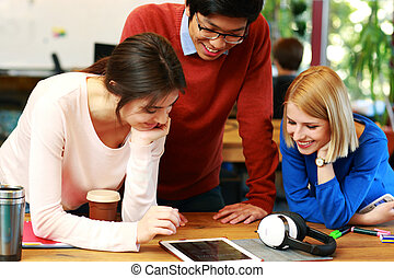 Cheerful students using tablet computer together